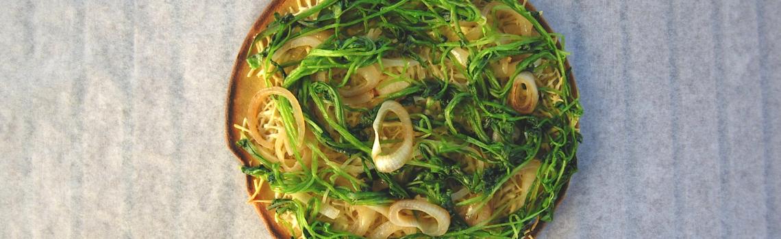 Glutenvrije pizza met winterpostelein en gekarameliseerde uien